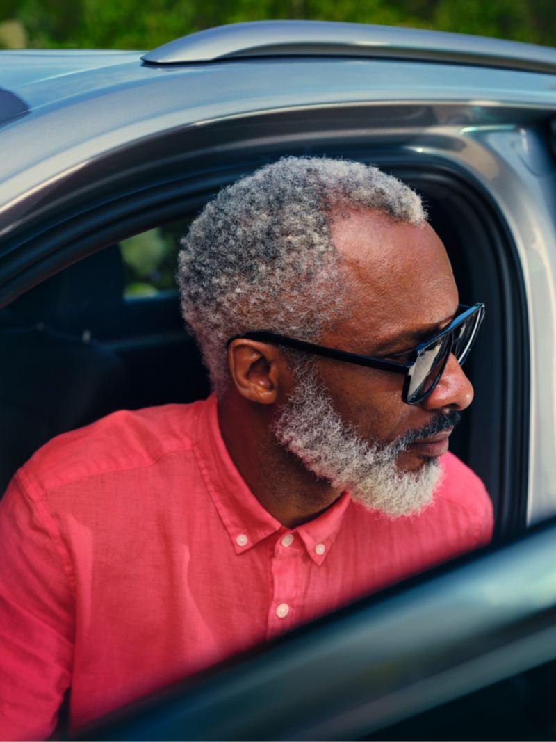 Hombre dentro de un Volkswagen Touareg e Hybrid asomándose por la ventanilla