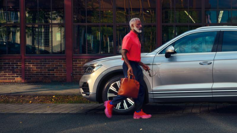 Hombre caminado delante de un Volkswagen Touareg eHybrid aparcado en la ciudad