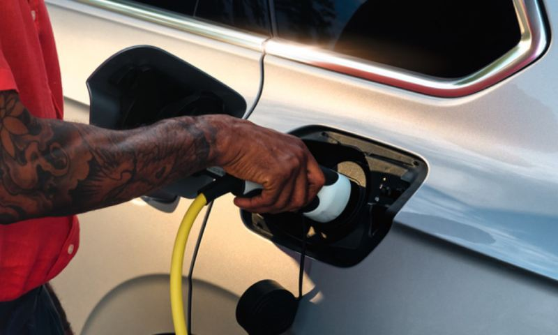 Primer plano de un hombre conectando el cargador eléctrico a un Volkswagen Touareg eHybrid