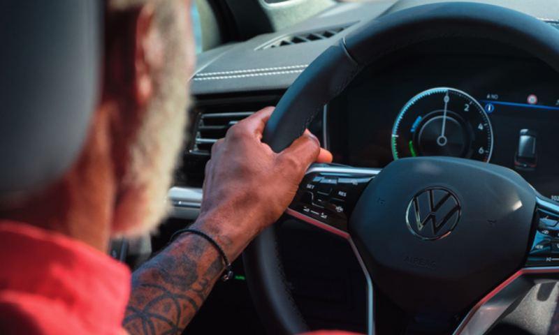 Primer plano de un hombre visto desde atrás conduciendo un Volkswagen Taourag eHybrid