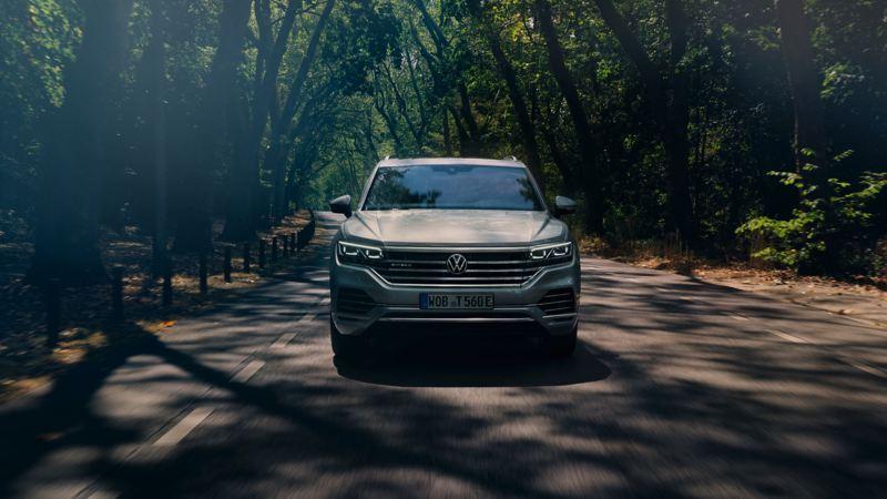 Vista frontal del Volkswagen Touareg eHybrid circulando por una carretera por un bosque