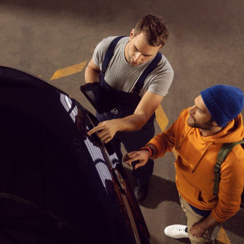 Mecánico y cliente hablando junto a un Volkswagen en un taller