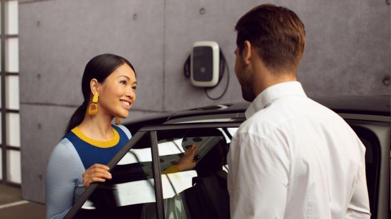 Mujer junto a la puerta abierta de un Volkswagen mientras habla con un mecánico