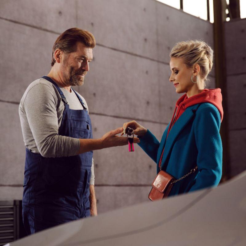 Mujer entregando las llaves de su Volkswagen a un mecánico