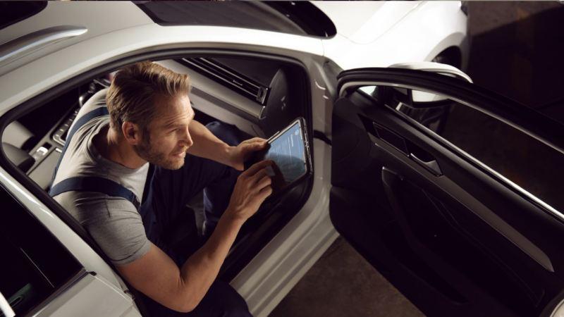 Mecánico con una tablet en el puesto del copiloto de un Volkswagen con la puerta abierta
