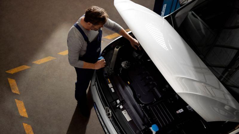 Mecánico visto desde arriba revisando el motor de un Volkswagen