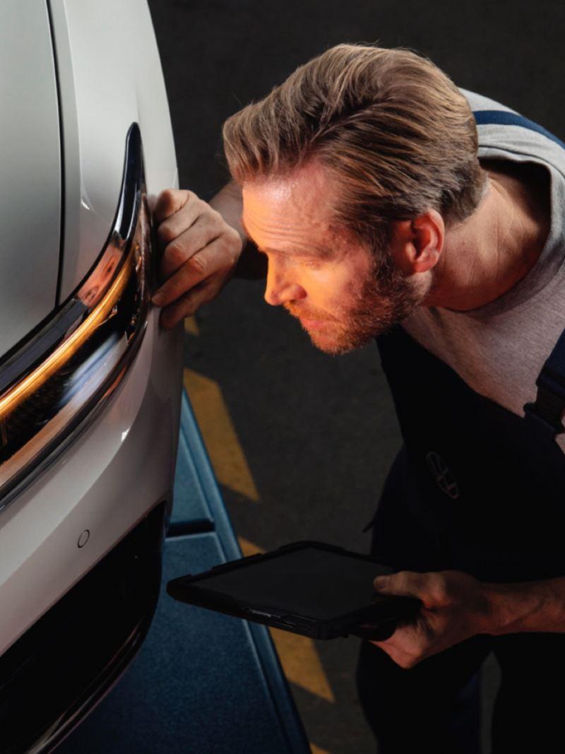 Mecánico con una tablet en la mano revisando el piloto de un Volkswagen