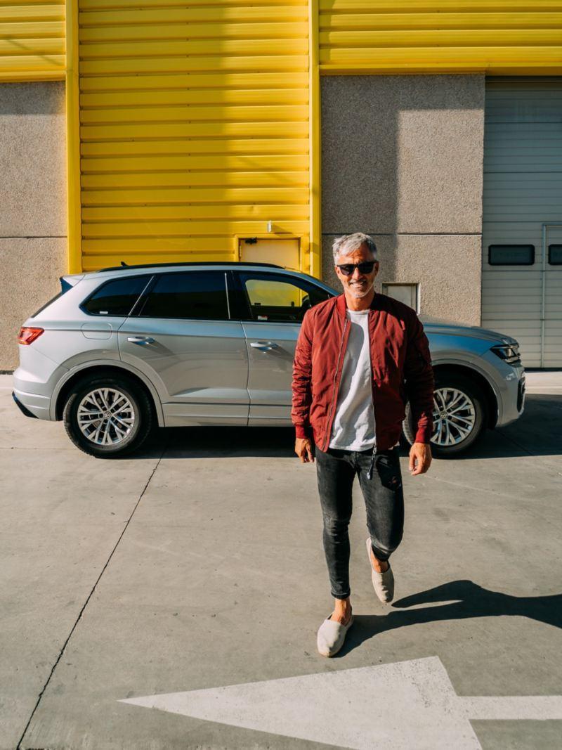 Hombre caminando con un SUV Volkswagen gris aparcado detrás