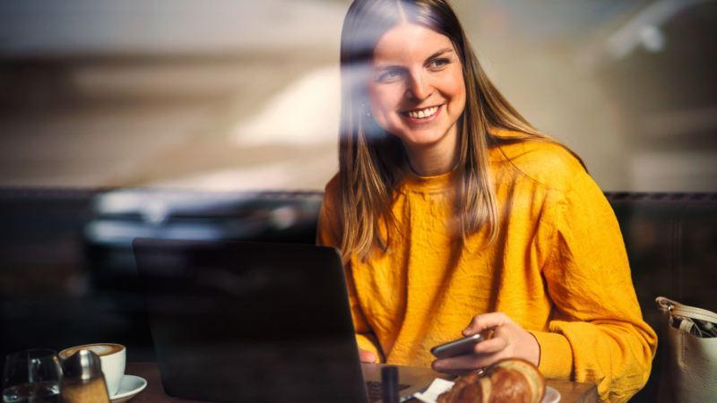 Mujer vestida de amarillo con un móvil en la mano y delante de un ordenador sonriendo