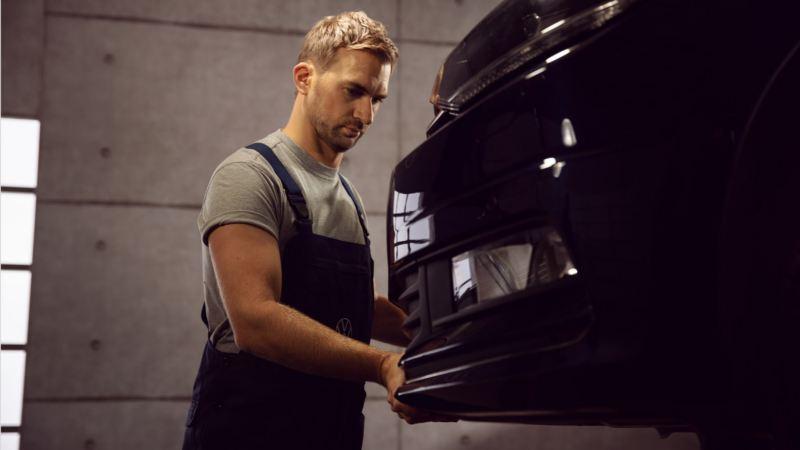 Mecánico revisando el paragolpes de un Volkswagen
