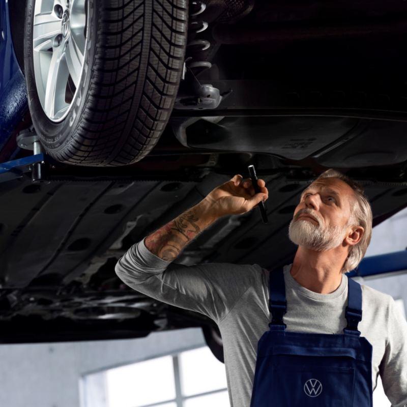 Mecánico revisando la parte inferior de un Volkswagen levantado en una grúa