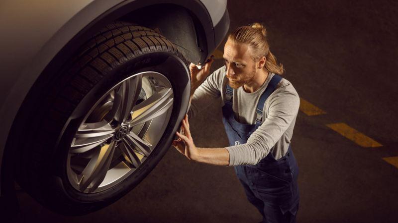 Mecánico con una linterna revisando el neumático de un Volkswagen levantado en una plataforma