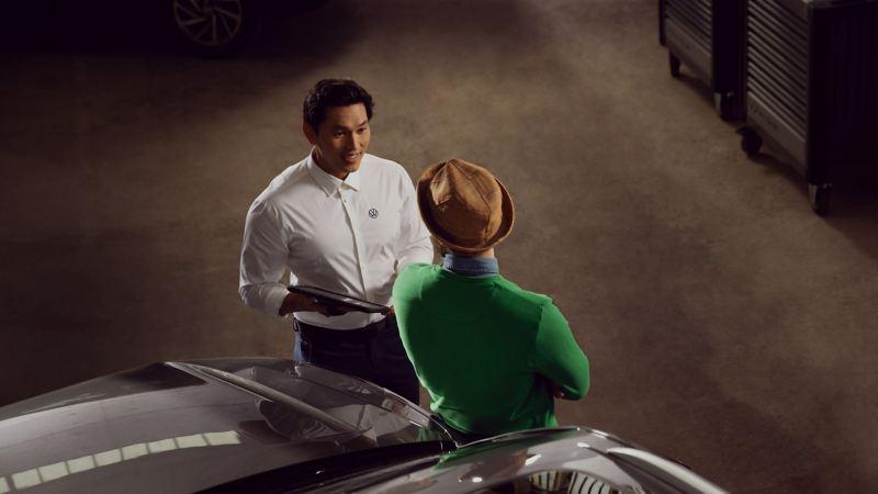 Mecánico hablando con un hombre joven apoyado en el capó de un Volkswagen visto desde arriba