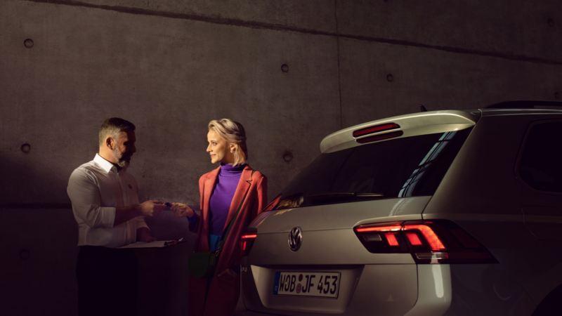 Mujer joven recibiendo las llaves de un Volkswagen Tiguan visto desde atrás