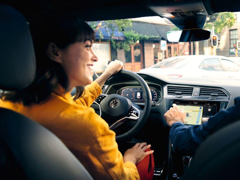 Mujer de amarillo sonriendo al volante de un Volkswagen vista desde el asiento de atrás