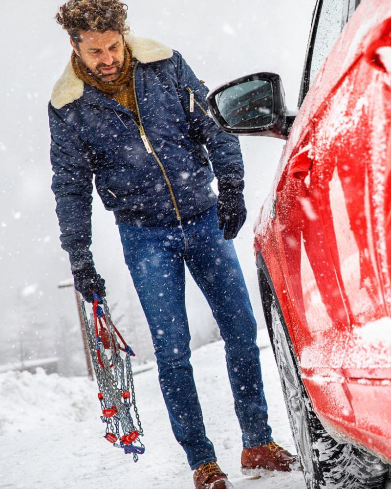 Hombre con cadenas de nieve en una tormenta junto a un Volkswagen rojo que se ve parcialmente
