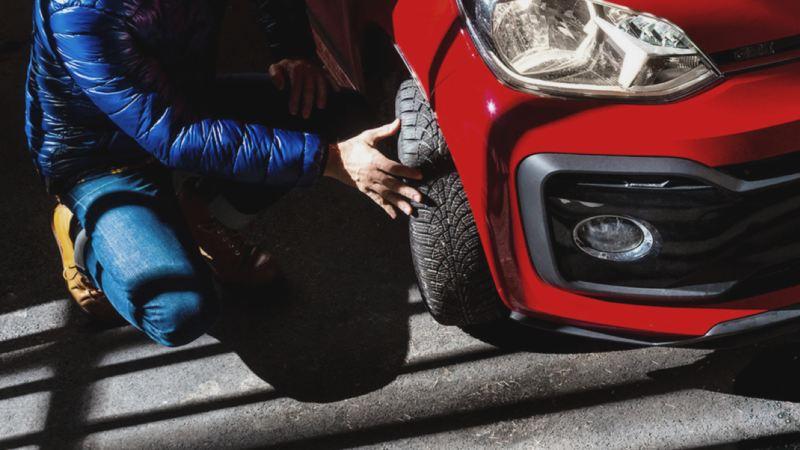 Primer plano de un hombre revisando un neumático de un Volkswagen rojo