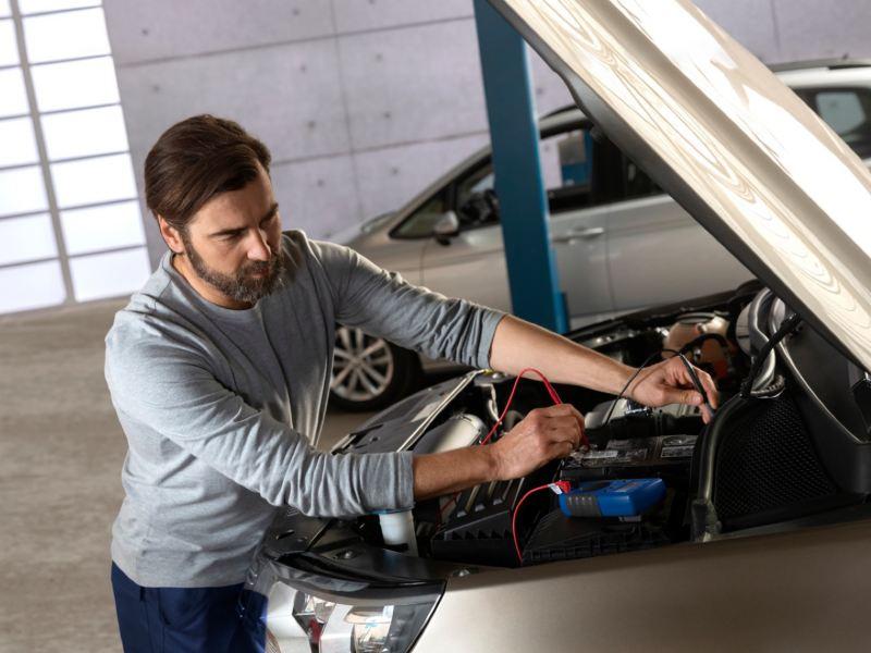 Mecánico probado una batería instalada en el motor de un Volkswagen