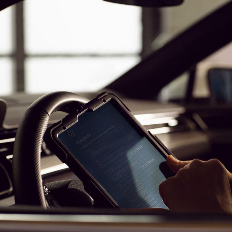 Detalle de una tablet y el volante de un Volkswagen