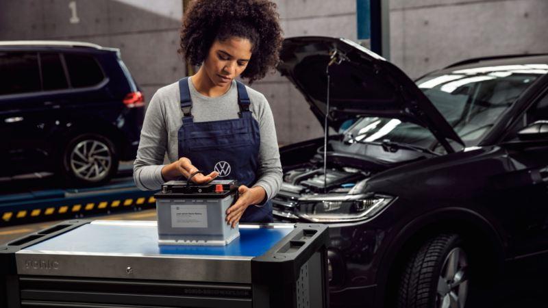 Mecánica examinando una batería en un taller delante de unos coches Volkswagen