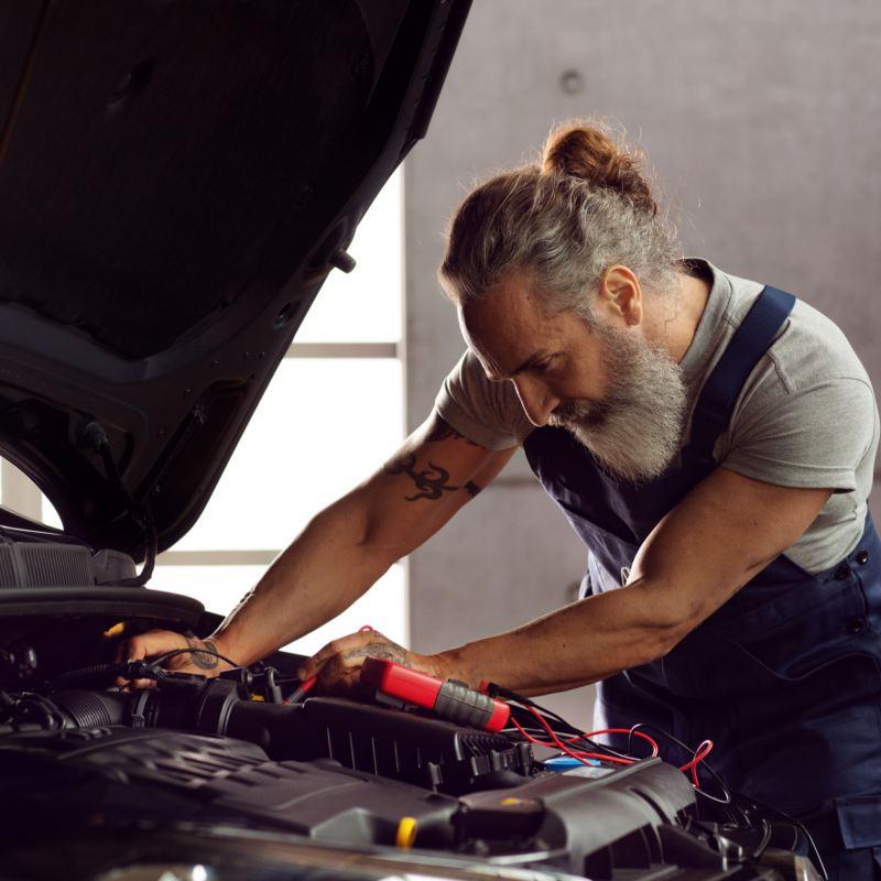 Mecánico con el capó abierto de un Volkswagen mirando la batería