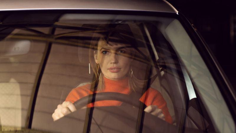 Mujer joven al volante de un Volkswagen vista a través del parabrisa