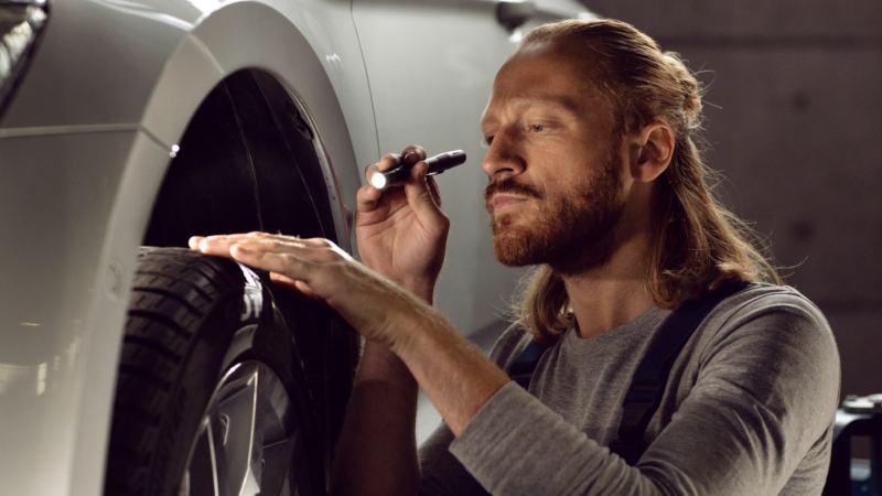 Primer plano de un mecánico revisando el estado de un neumático con una linterna en la mano