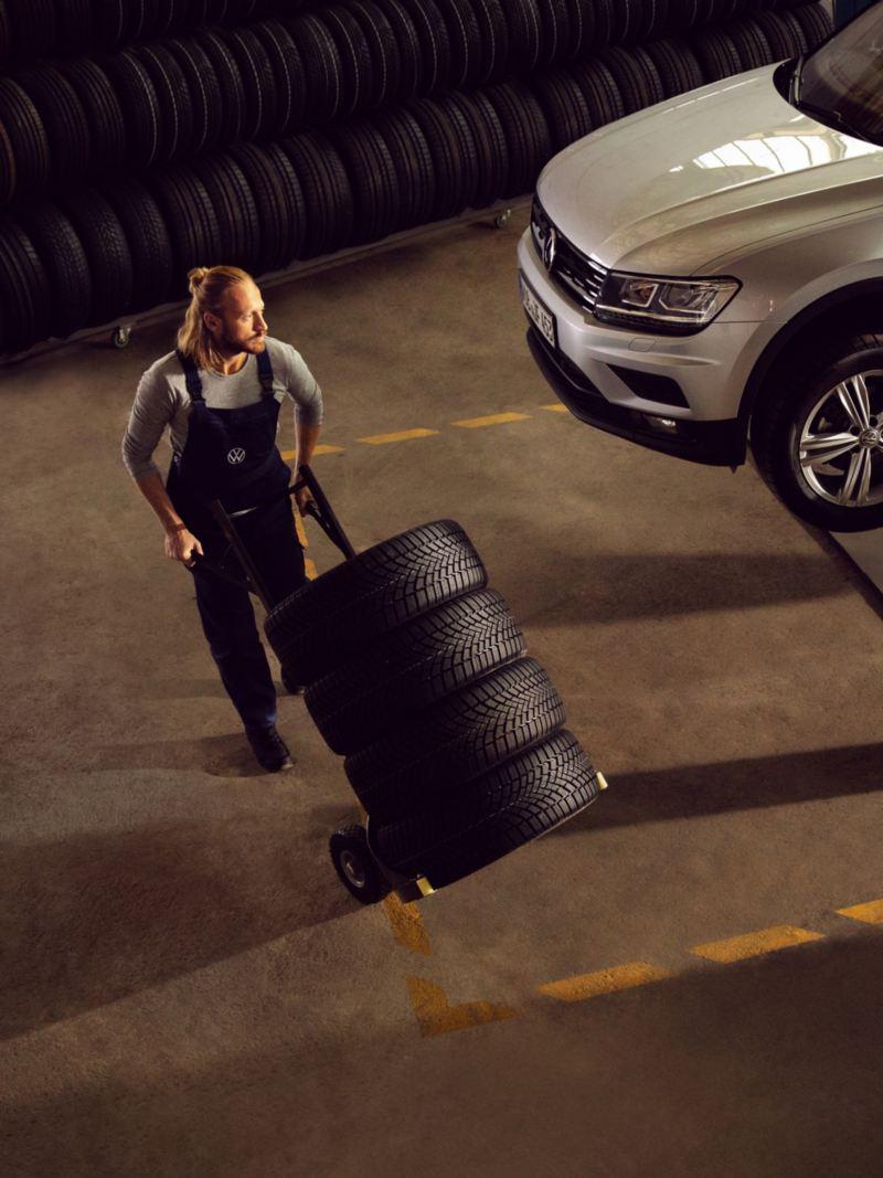 Vista superior de un mecánico llevando neumáticos en un carro