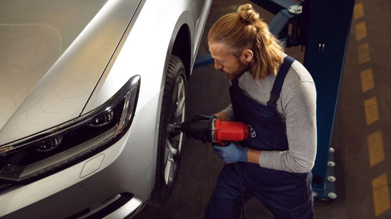 Mecánico fijando la tuerca de una llanta en un coche Volkswagen