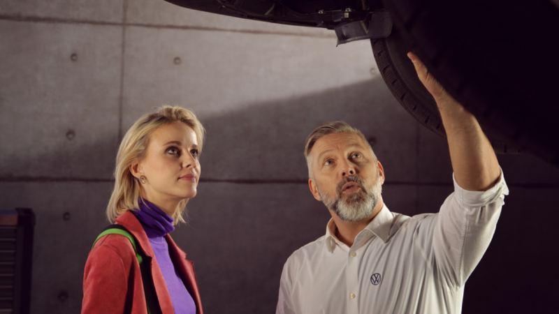 Mecánico mostrando el sistema de frenos de un Volkswagen a una mujer