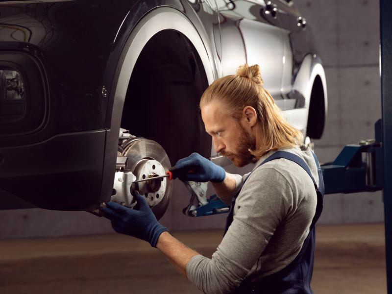 Hombre cambiando las pastillas de freno de un Volkswagen