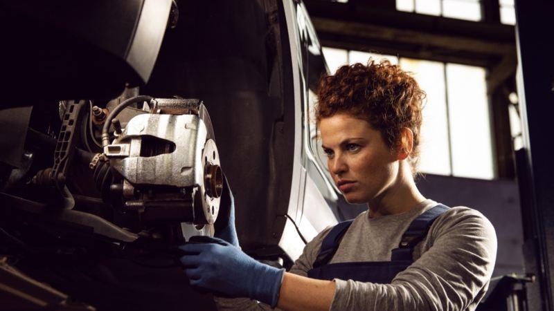 Mujer trabajando en los frenos de un Volkswagen