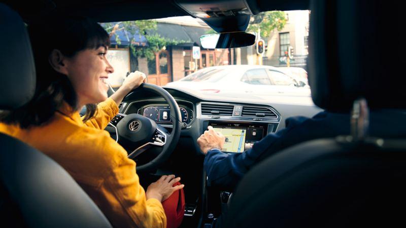 Chica sonriendo al volante de un Volkswagen vista desde el asiento de atrás