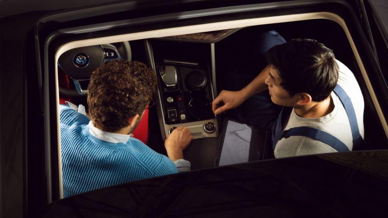 Propietario y mecánicos en el interior de un Volkswagen vistos desde arriba a través del techo solar