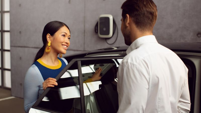 Mujer hablando con un asistente de Volkwagen junto a un coche con la puerta abierta en un taller