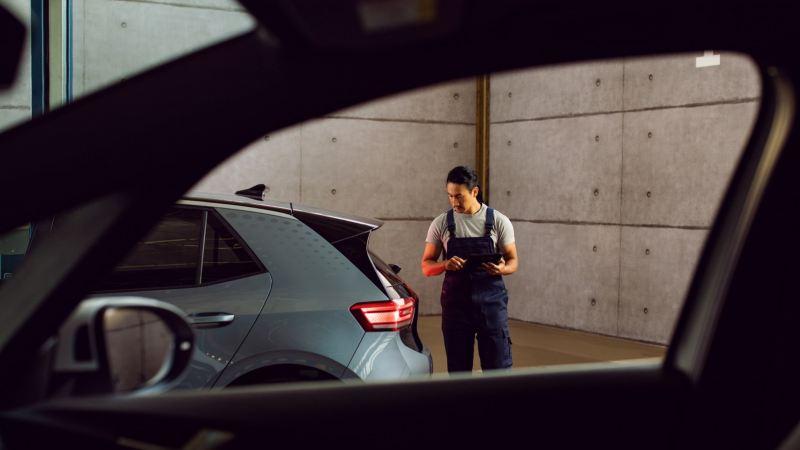 Mecánico revisando la parte trasera de un Volkswagen ID.3 visto desde el interior de otro coche
