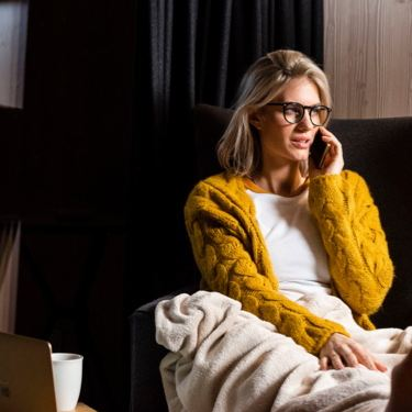 Mujer joven en un sillón con una manta hablando por teléfono