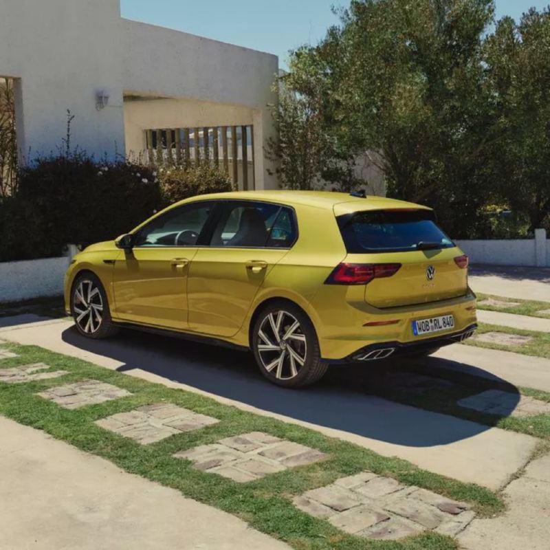 Vista trasera y lateral de un Volkswagen Golf 8 amarillo aparcado frente a una casa