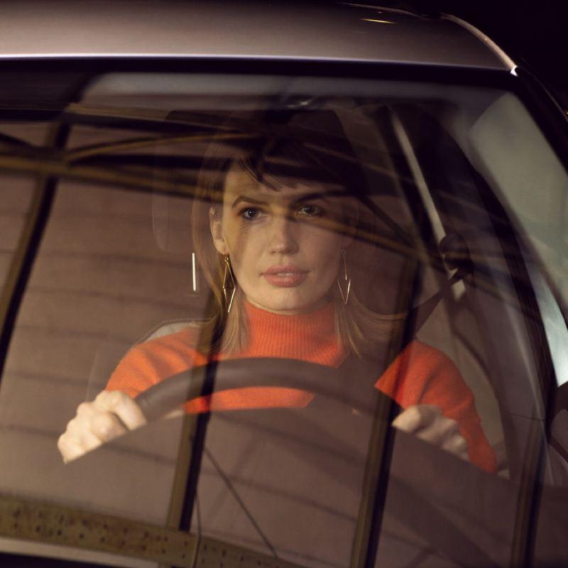 Vista frontal de una mujer con las manos al volante de un Volkswagen vista a través del cristal