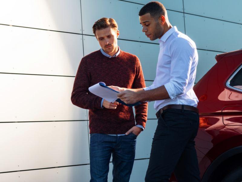 Agente oficial de Volkswagen atendiendo a una cliente junto a un Volkswagen en la puerta del concesionario