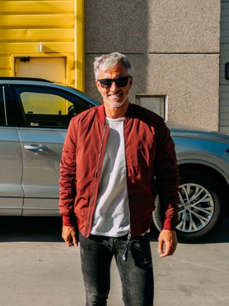 Hombre con gafas de sol mirando a la cámara sonriendo junto a un Volkswagen aparcado en la calle