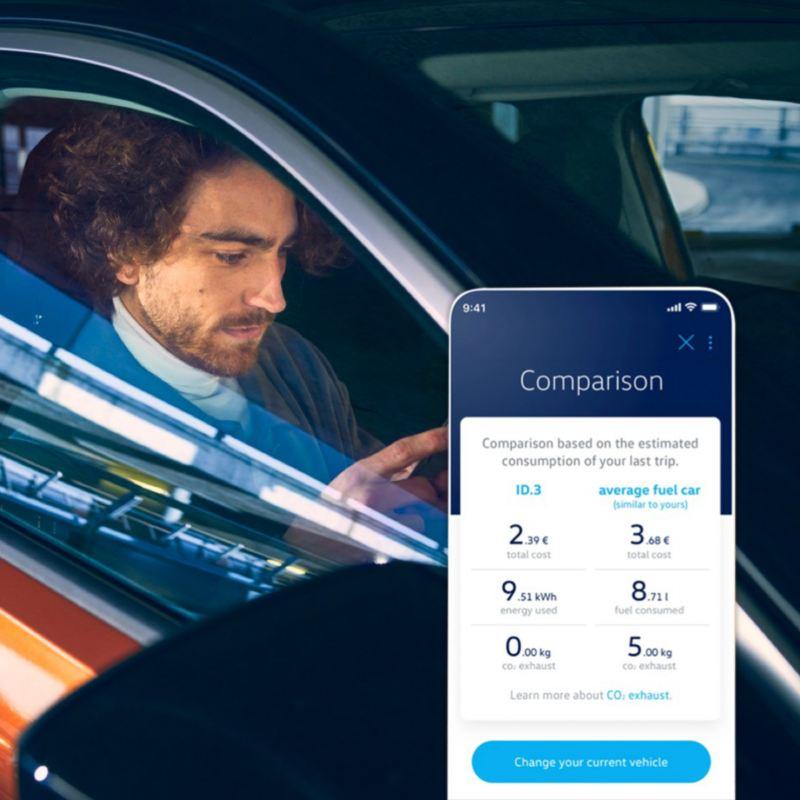 Móvil con la aplicación EV Check en la pantalla delante de un hombre sentado dentro de un Volkswagen