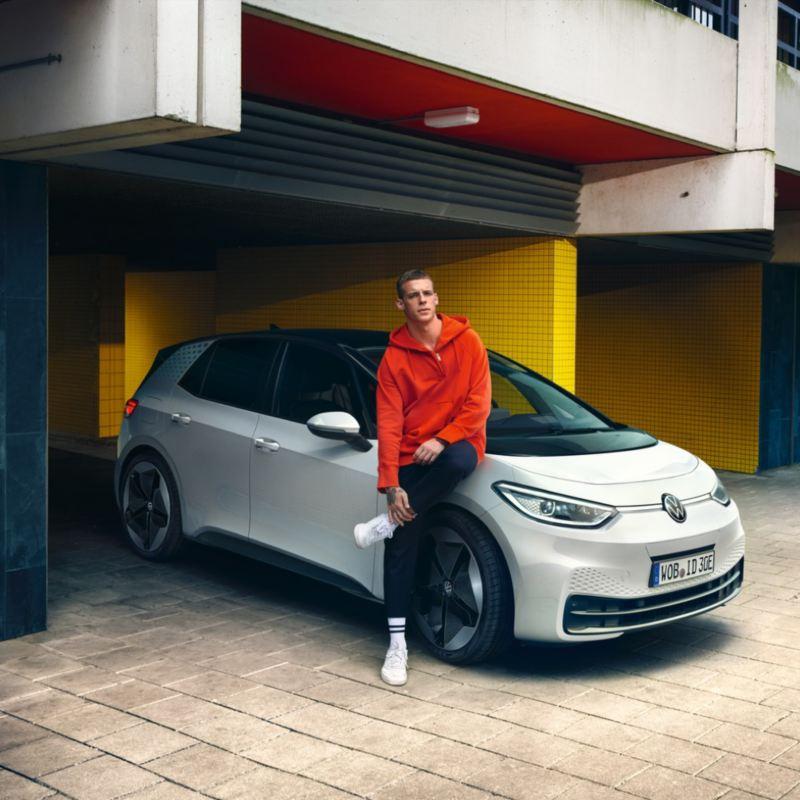 Chico joven apoyado sobre un Volkswagen ID.3 blanco aparcado