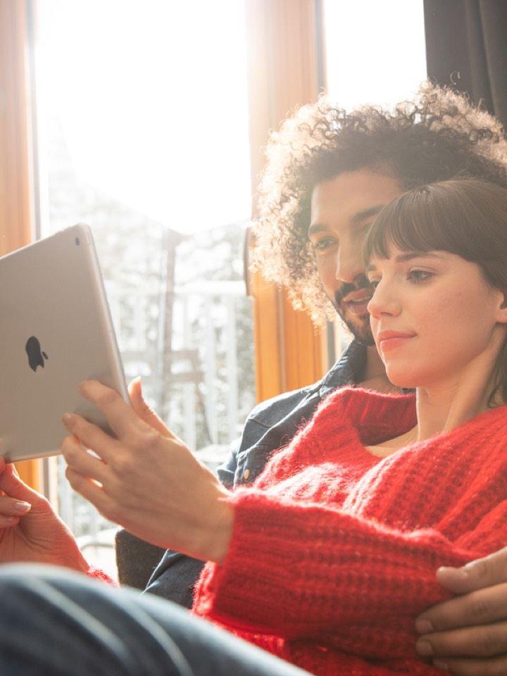 Pareja joven sentada en un sofá con una tablet