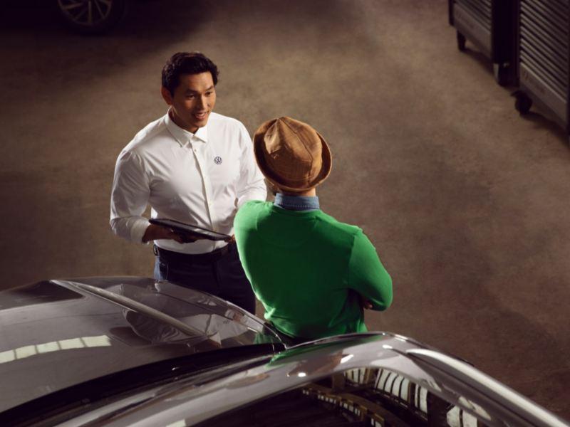 Hombre apoyado en un Volkswagen mientras habla con un representante de Volkswagen vistos desde arriba