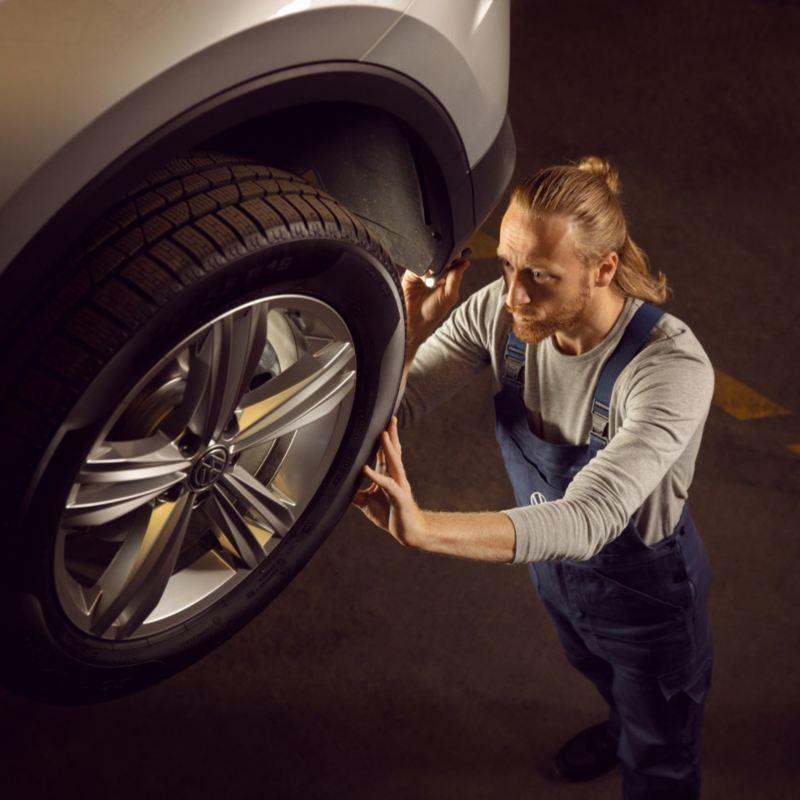Mecánico revisando los neumáticos de un Volkswagen