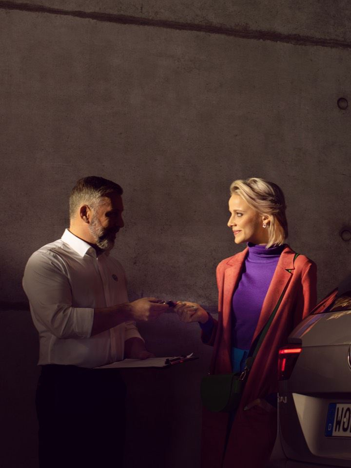 Mujer recibiendo las llaves de un Volkswagen de parte del encargado