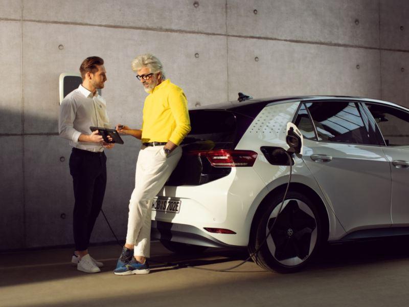 Asistente de Volkswagen hablando con un hombre apoyado en la parte trasera de un ID.3