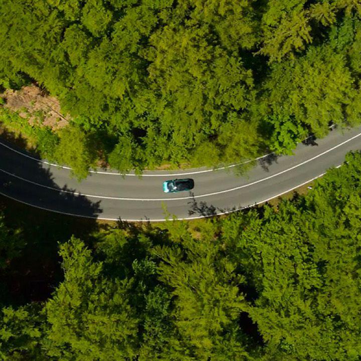 Vista desde el aire de un Volkswagen en una carretera que atraviesa un bosque