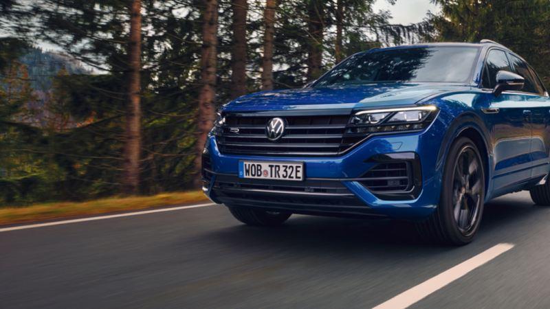 Vista frontal de un Volkswagen Touareg R circulado por una carretera en el bosque